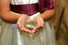 Young girl in dress holding heart shaped stone Royalty Free Stock Images