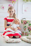 Young girl in a dress, playing with her doll Stock Photos