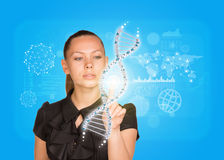 Young girl in dress pushing finger on model of DNA Stock Photo