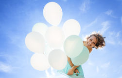 Young girl in a dress, smiling and laughing holding balloons. Against the sky Stock Image