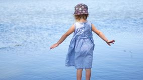 Young girl in dress standing with open arms at lakeside.  stock video footage