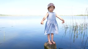 Young girl in dress standing with open arms at lakeside.  stock footage