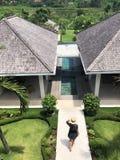 Young girl in dress walking at tropical villa resort stock photo