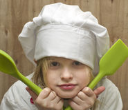 Young girl dressed as chef with green silicone spoons on wooden Stock Image