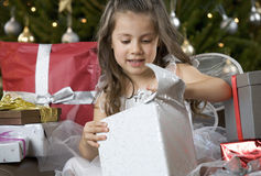 A young girl dressed as a fairy opening a Christmas present Royalty Free Stock Images