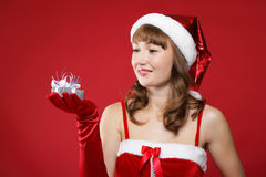 Young girl dressed as Santa holds a gift. Stock Image