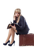 Young girl dressed in business suit, sitting on suitcase reading. Beautiful young girl dressed in a business suit, sitting on a suitcase and reading a magazine royalty free stock image