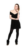 Young girl dressed in casual black dress and black sneakers Royalty Free Stock Photos