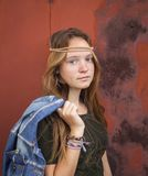 Young girl dressed in hippie style, against a background of burgundy metal wall. Royalty Free Stock Image