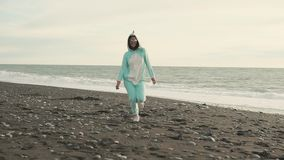 Crazy woman is wearing kigurumi costume of the unicorn is running over beach. Young girl is dressed in kigurumi of blue unicorn is fleeing funny on a sea coast stock video footage
