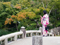 Young girl dressed in kimono in traditional Japanese garden royalty free stock photos