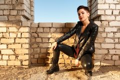 Young girl dressed in leather clothing, posing in abandoned building stock photography
