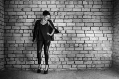 Young girl dressed in leather clothing, smoking in empty abandon. Ed room stock photos