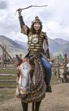 Young girl dressed like a mongol warrior on ahorse. Lake Issyk-Kul, Kyrgyzstan, 6th September 2018: girl in mongol warrior outfit during World NOmad Games 2018 stock images