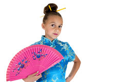 Young girl dressed in oriental gown holding a fan Royalty Free Stock Photography
