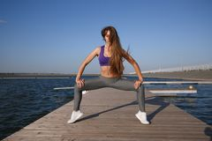 Young girl dressed in sports clothes doing plie squat on the wooden pier outdoor royalty free stock photo