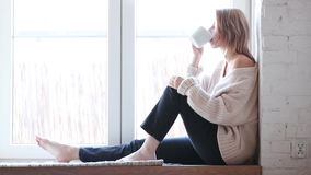 Girl with cup of coffee sitting near window stock video footage
