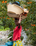 A young girl dressed in traditional way, carrying dishes on her head Royalty Free Stock Images