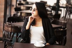 Young girl drinking black coffee. In empty cafe bar Royalty Free Stock Photo