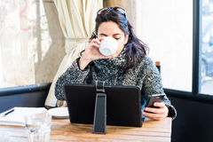 Young girl drinking cappuccino and looking at smartphone Stock Photos