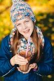Young girl drinking chocolate milkshake in autumn park Stock Photos