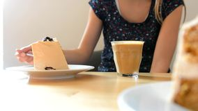 Young girl drinking coffee in a cafe. stock footage