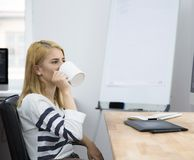 Young girl drinking coffee in office Royalty Free Stock Image