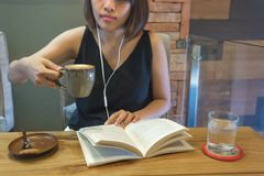 Young girl drinking coffee and reading book royalty free stock photo