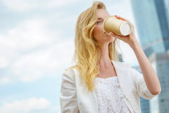 Young girl in drinking coffee in the street Royalty Free Stock Photos
