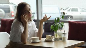 Young girl drinking coffee and talking on mobile phone in cafe. business woman discussion of business matters on lunch break Stock Image