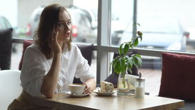 Young girl drinking coffee and talking on mobile phone in cafe. business woman on lunch break. A young beautiful woman drinking coffee in a cafe. young woman in stock video footage