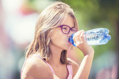 Young girl drinking fresh water on a hot summer day Stock Photography