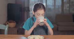 Young girl drinking a glass of milk stock footage