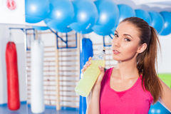 Young girl drinking isotonic drink, gym.  Royalty Free Stock Image