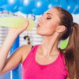 Young girl drinking isotonic drink, gym.  Royalty Free Stock Photo