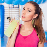 Young girl drinking isotonic drink, gym.  Stock Image