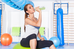 Young girl drinking isotonic drink, gym. She is happy Stock Photography
