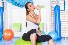 Young girl drinking isotonic drink, gym. She is happy Royalty Free Stock Images
