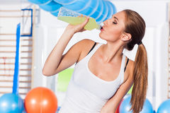 Young girl drinking isotonic drink, gym. She is happy. And full of emotion Stock Image