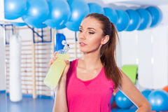 Young girl drinking isotonic drink, gym. She is happy and full o. F positive emotion Royalty Free Stock Photos