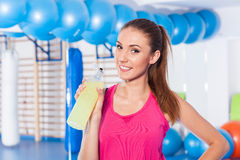 Young girl drinking isotonic drink, gym. She is happy and full o Royalty Free Stock Images