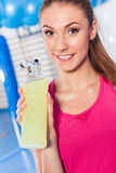 Young girl drinking isotonic drink, gym. She is happy and full o. F positive emotion Stock Image