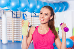 Young girl drinking isotonic drink, gym. She is happy and full o. F positive emotion. She is holding dumbbell Royalty Free Stock Photo