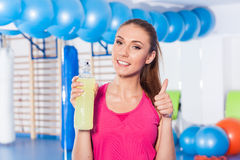 Young girl drinking isotonic drink, gym. She is happy and full o. F positive emotion. Thumb up Royalty Free Stock Photos