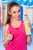 Young girl drinking isotonic drink, gym. She is happy and full o. F positive emotion. Thumb up Royalty Free Stock Photography