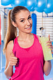 Young girl drinking isotonic drink, gym. She is happy and full o. F positive emotion. Thumb up Stock Images