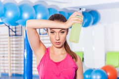 Young girl drinking isotonic drink, gym. She is wiping sweat Stock Photos