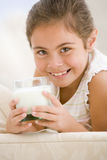 Young girl drinking milk in living room smiling royalty free stock photography