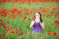 Young girl drinking milk in a poppy field Royalty Free Stock Image