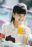 Young girl drinking orange juice in cafe Stock Photo